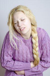 リーキーガット症候群で腹痛に苦しむ女性